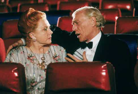 Medium shot of Richard Harris as Frank, wearing tuxedo, facing and with arm around Shirley MacLaine as Helen Cooney; both seated in empty theater. Photo by Warner Bros./Getty Images.