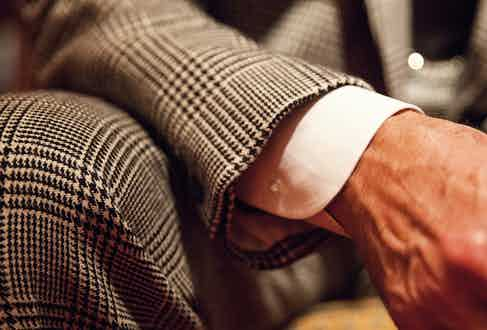 A classic button-cuff shirt — and all the working buttonholes buttoned on his jacket — are a must. He never wears a wristwatch with a suit, only a pocket watch.