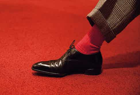 While his suits tend to be sober, he injects color with his socks. He has an appreciation for shoes but keeps it simple with a bench-made cap toe here. Anchoring the look to the ground are highly polished and elegant Oxfords from British shoemakers Gaziano & Girling.