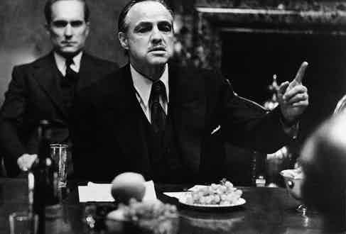 Marlon Brando with Robert Duvall sat behind him in a still from the film, 'The Godfather'. Photo by Paramount Studios/Courtesy of Getty Images.