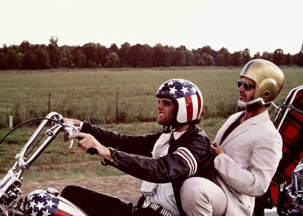 Peter Fonda, wearng a stars-and-stripes helmet, and Jack Nicholson, wearing a gold American football helmet, as they ride Fonda's chopper motorcycle in a publicity still issued for the film, 'Easy Rider', USA, 1969. Photo by Silver Screen Collection/Getty Images.