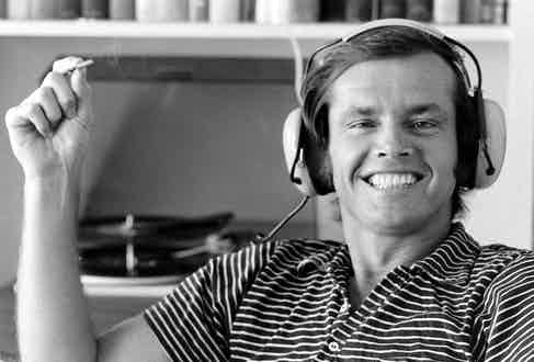 American film actor Jack Nicholson grins broadly as he smokes and listens to music on a pair of headphones in his home, Los Angeles, California, 1969. Photo by Arthur Schatz/The LIFE Picture Collection/Getty Images.