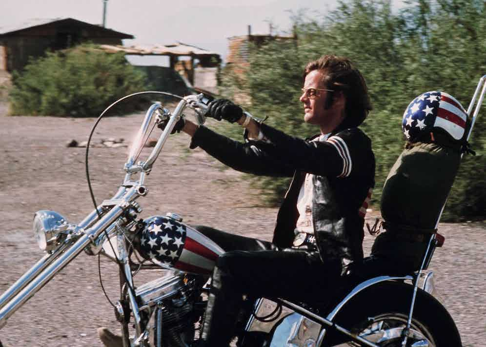 Peter Fonda riding a chopper motorcycle, with a stars-and-stripes helmet on the backrest of his seat, in a publicity still issued for the film, 'Easy Rider', USA, 1969. Photo by Silver Screen Collection/Getty Images.