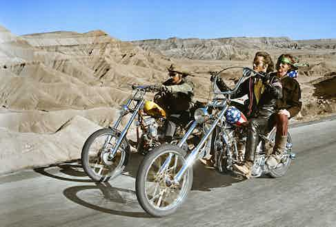 Dennis Hopper (1936-2010), US actor, and Peter Fonda, US actor, riding their chopper motorcycles, with Luke Askew, US actor, on the back of Fonda's motorcycle, in a publicity still issued for the film, 'Easy Rider', USA, 1969. Photo by Silver Screen Collection/Getty Images.