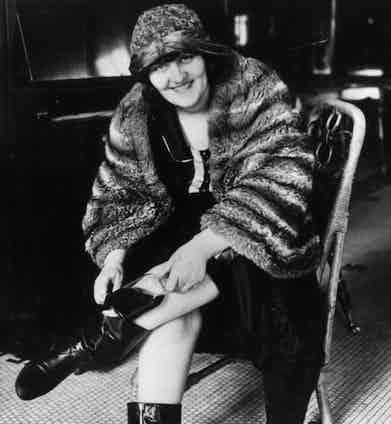 January 1922:  A woman putting a hip flask, known as the ankle-flask, into her Russian boot which fastens at the ankle, one of the many ways people have found of avoiding the strict prohibition laws in America. Photo by Hulton Archive/Getty Images.