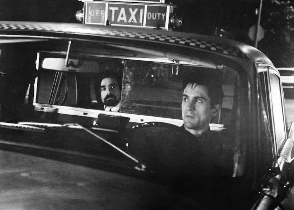Director Martin Scorsese (left) as the 'Silhouette Watching Passenger', and Robert De Niro as Travis Bickle in 'Taxi Driver', directed by Scorsese, 1976. Photo by Silver Screen Collection/Getty Images.