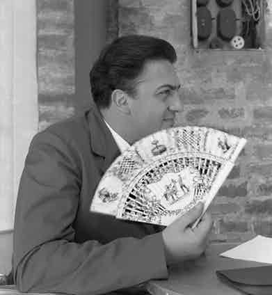 Italian director Federico Fellini wearing a suit, portrayed while holding a fan, Venice, 1954. Photo by Archivio Cameraphoto Epoche/Getty Images.