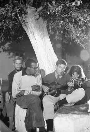 Leonard Cohen playing guitar on his right is Marianne Ihlen in Hydra, Greece where he bought a vacation home, October 1960. Photographer: James Burke Time Inc/Merlin.