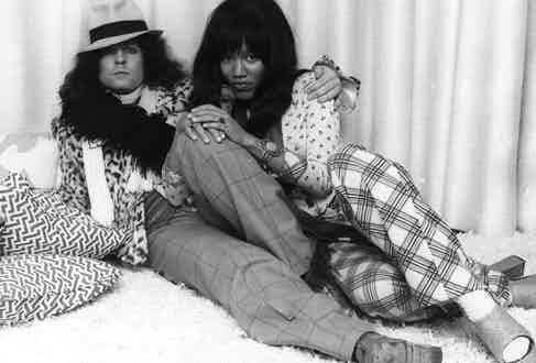 British singer, songwriter and guitarist Marc Bolan, of the pop group T Rex, reclines with his girlfriend, singer Gloria Jones, 1974. Photo by Keystone/Getty Images.