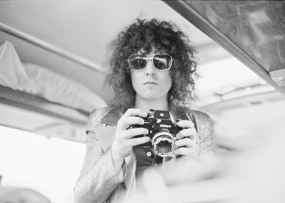 Singer Marc Bolan of English glam rock group T-Rex, holding a Nikon camera on a tour bus during a four-date British tour, June 1972. Photo by Michael Putland/Getty Images.