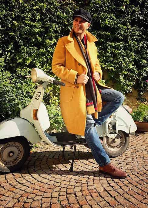 Luca Rubinacci (of the eponymous tailoring brand) takes the Casentino for a spin on his vespa and dresses the coat down with jeans and a peaked cap.