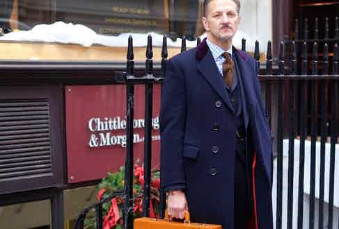 Believe it or not, Clive's hefty covert coat is well over fifty years old. One of his prized vintage finds, its tailored in bulletproof midnight blue serge and is trimmed in a dashing crimson satin lining. It was made by Bernard Weatherill in the 60s.