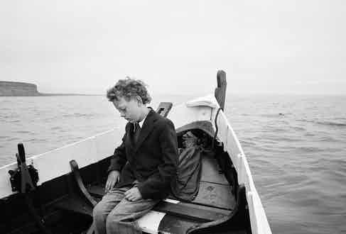Simon being taken to sea for the first time since his father drowned, Skinningrove, North Yorkshire, 1983, by Chris Killip.