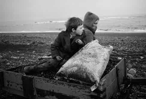 Rocker and Rosie Going Home, Seacoal Beach, Lynemouth, 1984, by Chris Killip.