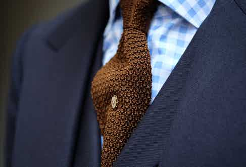In rakish fashion, Clive is a fan of strong checked shirts and wide spread collars. The tie is a glorious copper knitted silk piece from Turnbull & Asser, and the pin was another piece of his grandfather's.