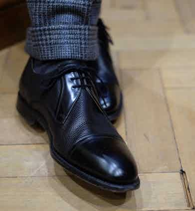 """""""I bumped into your Editor, Tom Chamberlin the other day, and he spotted my shoes and said 'You wore those to your daughter's wedding!' It's fitting that he would notice that sort of thing,"""" David laughs as he points to his Barker shoes. The black leather vamps have a subtle grain, which softens the formality of the shoes and brings out the texture of his suit. """"I tend to go for fairly classic styles – I'd love to be able to wear more Italian style shoes but a cycle accident a few years ago messed up one of my feet. I do find that the more you spend on shoes the more comfortable they are – Edward Green's are so slim and beautiful, but feel so good.""""  David's London Sock Co. socks peep unassumingly out from beneath his tailored turn-ups."""