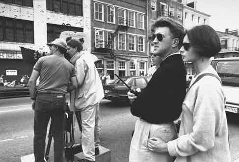 Movie director David Lynch, wearing sunglasses, holding walkie-talkie as he oversees camera crew while his girlfriend, actress Isabella Rossellini stands behind him w. her hands on his hips, during filming of movie Wild at Heart. Photo by Acey Harper/The LIFE Images Collection/Getty Images.