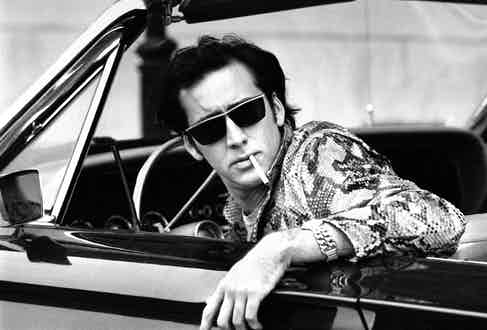 Nicolas Cage, wearing sunglasses and snakeskin jacket, w. cigarette hanging out of his mouth as he sits in convertible during filming of movie Wild at Heart; New Orleans. Photo by Acey Harper/The LIFE Images Collection/Getty Images.
