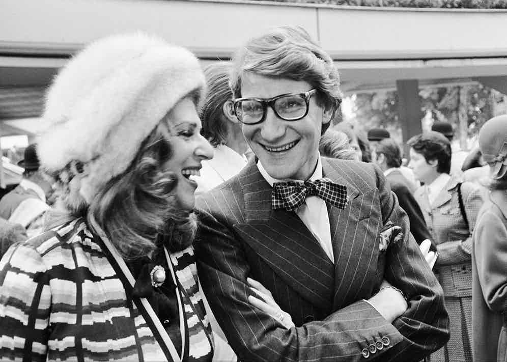 Baroness Rothschild laughing with Yves Saint Laurent at the Longchamp racecourse, 1973 (Photo via Getty)