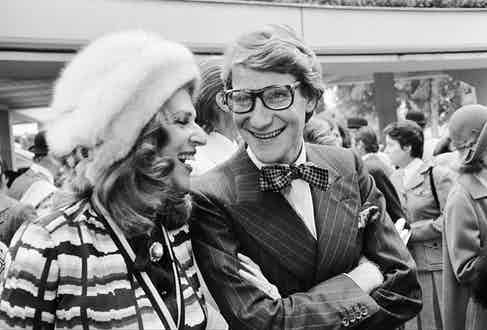 Baroness Rothschild laughing with Yves Saint Laurent at the Longchamp racecourse, 1973.