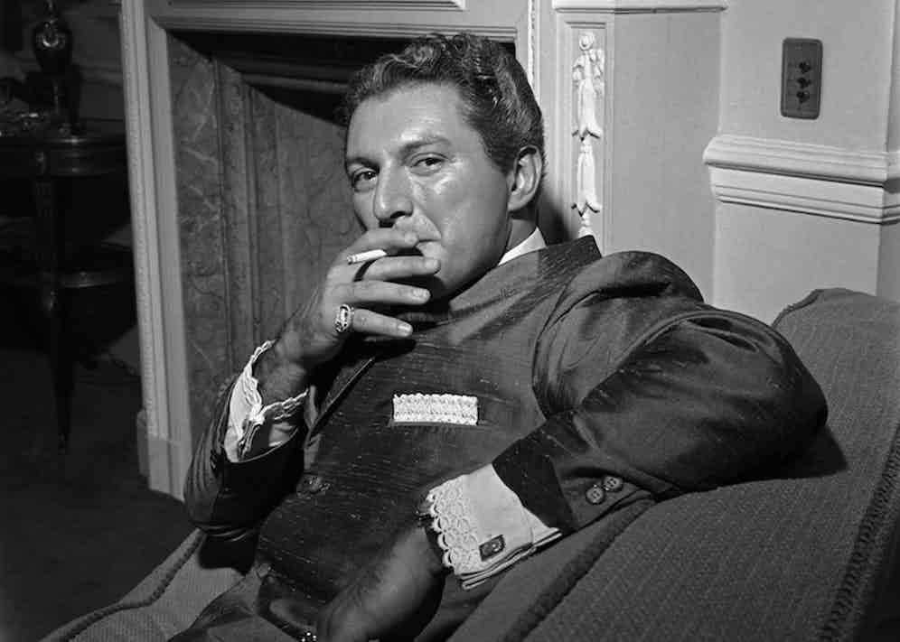 Liberace, posed, in hotel room, 1960. Photo by Harry Hammond/V&A Images/Getty Images.