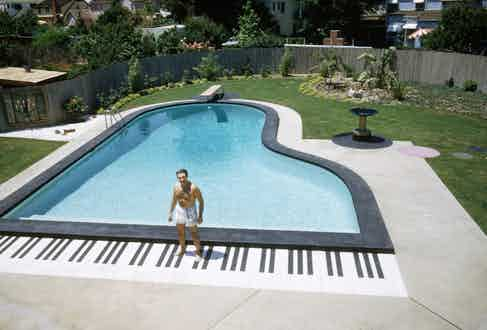 Valentino Liberace standing next to his swimming pool which is shaped like a piano. Los Angeles, California July 1954. Photograph by Loomis Dean Time Inc/Owned by Merlin.