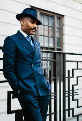 """Shaun wears a bespoke Turnbull & Asser navy herringbone double-breasted suit. He says: """"I felt like it was time in my life to have the typical navy, two piece suit which I didn't actually have. So I said to Michael in the shop that I needed one."""" Shaun chose the fabric and selected the cut, which represents T&A's signature double-breasted model, with a two-by-three button-stance, high-break, slanting flap pockets and trim peaked lapels."""