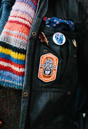 """As you might have noticed, Dean isn't afraid to add small personal touches and extra elements to his ensemble. Here, he collides an elegant poppy, own-brand pocket hanky that sits in front of his grandfather's military bar. """"They have been the inspiration for a lot of shirt designs, because the colour palette we use has a rich history in military uniforms,"""" Dean adds."""