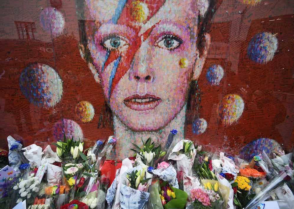 Flowers and tributes are placed by an art work of David Bowie, on his first death anniversary in Brixton, London, 10 January 2017. Photo by Facundo Arrizabalaga/EPA/REX/Shutterstock.