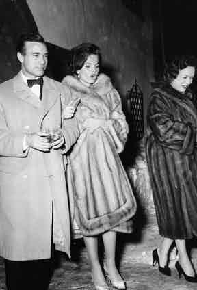 Diplomat and racing driver Porfirio Rubirosa and his wife Odile Rodin (centre) leaving the night club 'Chesa Veglia' in Saint Moritz in Switzerland, circa 1960. Photo by Keystone/Hulton Archive/Getty Images.