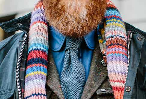 """Perhaps the highlight of Dean's ensemble is his scarf, which instantly grabs your attention, and its provenance is deeply endearing. """"It's a family tradition. My wife is Swedish and when you join the family you get a scarf that has been knitted. So these are all my wife's jumpers from when she was little. They've been unpicked and then stitched into a scarf."""" It somehow pairs well with his shirt-tie combo, both items of which are, of course, Turnbull & Asser. The shirt is a denim-cashmere blend, a fabric that Dean developed in-house, whilst the tie is a wool-cashmere old favourite from a few seasons ago."""