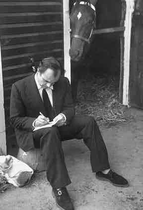 Aly Khan writing on piece of paper before horse auction. Photo by Ralph Morse/The LIFE Picture Collection/Getty Images.