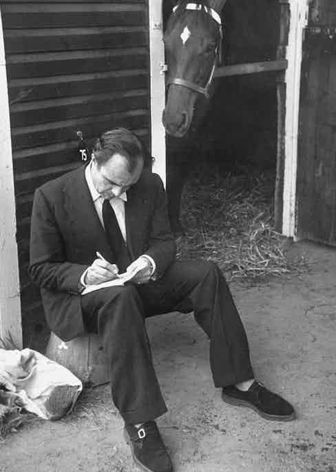 Prince Aly Khan writing on piece of paper before horse auction. (Photo by Ralph Morse/The LIFE Picture Collection/Getty Images)