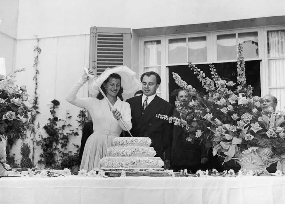 Prince Aly Khan watching bride, actress Rita Hayworth cutting into their wedding cake with a glass sword at Khan's Riviera Chateau de L'Horizon. Photo by Nat Farbman/The LIFE Picture Collection/Getty Images.
