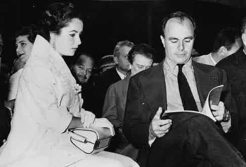 Prince Aly Khan reading the item catalogue, sitting next to actress Elizabeth Taylor, at an auction of his paintings in Paris, May 23rd 1957. Photo by Keystone/Hulton Archive/Getty Images.