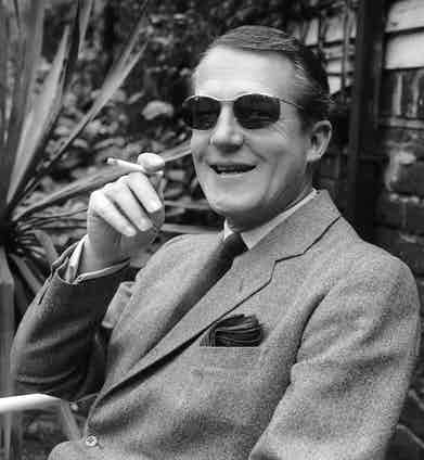 Hardy Amies relaxes outdoors. Photo by A. Jones/Evening Standard/Getty Images.