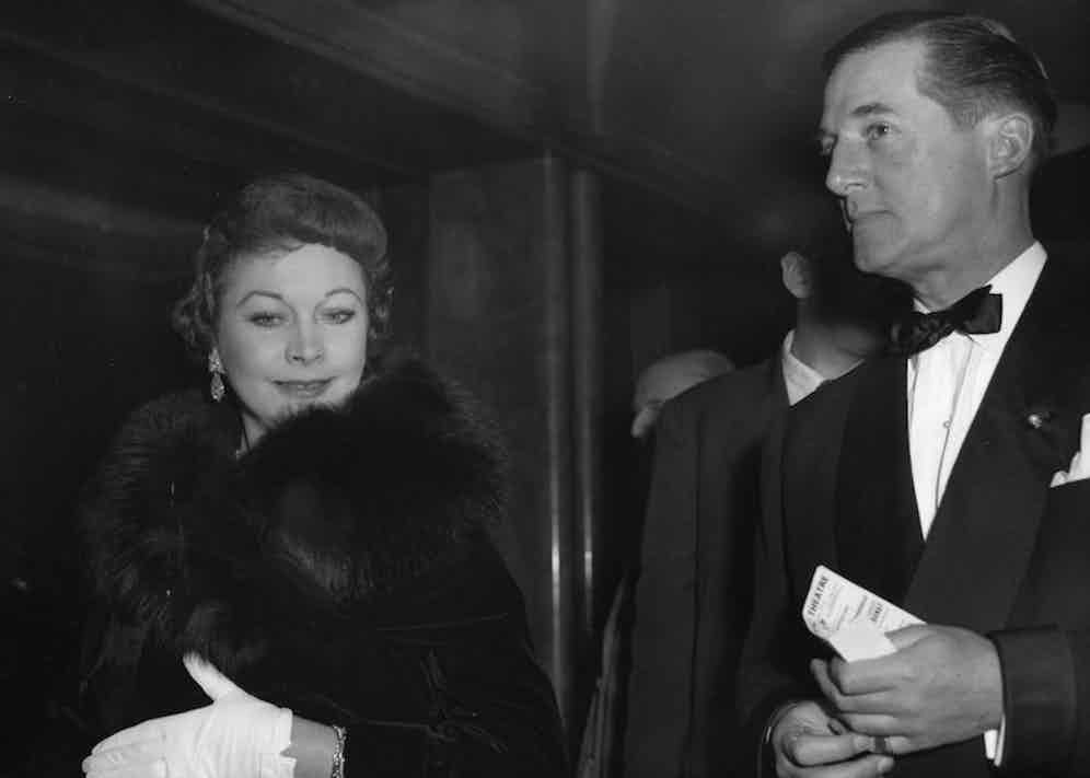 Hardy Amies accompanies actress Vivien Leigh to a film premiere in Leicester Square in 1958. Photo by AP/REX/Shutterstock.
