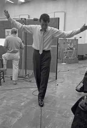 During a recording session, American actor and musician Dean Martin 'balances' on a straw power cord as he clowns about in a studio, Los Angeles, California, 1958. Photo by Allan Grant/The LIFE Picture Collection/Getty Images.