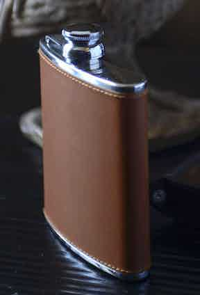 A leather-bound hip flask by Ettinger.