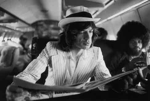 Mick Jagger keeps abreast of current affairs while travelling between concerts in the Rolling Stones' private jet during their 1975 Tour of the Americas. Also aboard is American keyboard player Billy Preston (right). Photo by Christopher Simon Sykes/Hulton Archive/Getty Images.