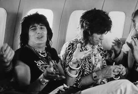 Guitarists Ron Wood (left) and Keith Richards in the Rolling Stones' private jet during the group's 1975 Tour of the Americas. Photo by Christopher Simon Sykes/Hulton Archive/Getty Images.
