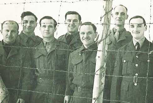 Gerald Imeson behind barbed wire at Stalag Luft III (centre back).