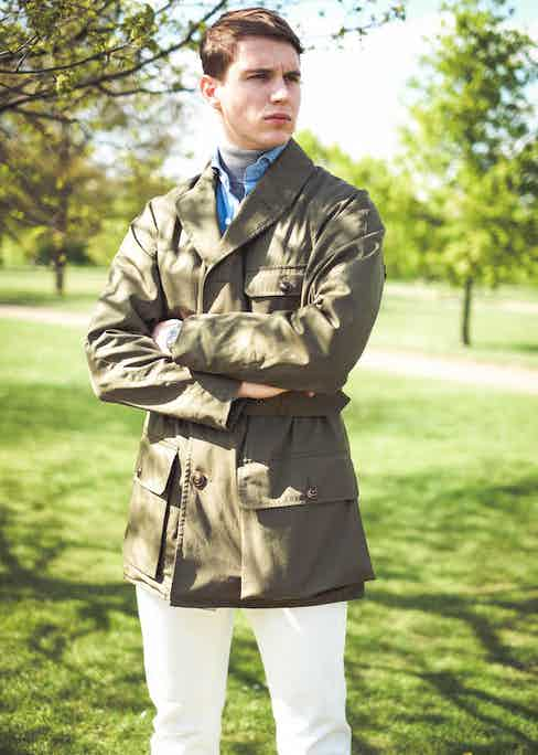 Shooter Jacket by Grenfell x The Rake; powder blue denim shirt, Drake's for The Rake; grey roll neck, Sunspel; white jeans, Dunhill; Chelsea boots, Crockett & Jones; bag, Troubabdour; sunglasses, watch and ring property of the stylist.