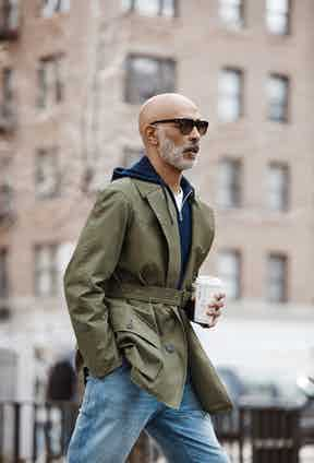 Laundered green Grenfell cloth cotton Shooter jacket, Grenfell for The Rake; navy cotton Guernsey knit, zip front hooded jumper, Orlebar Brown; white linen T-shirt, Timothy Everest; camouflage acetate Lord sunglasses with a gradient lens, Oliver Goldsmith for The Rake.