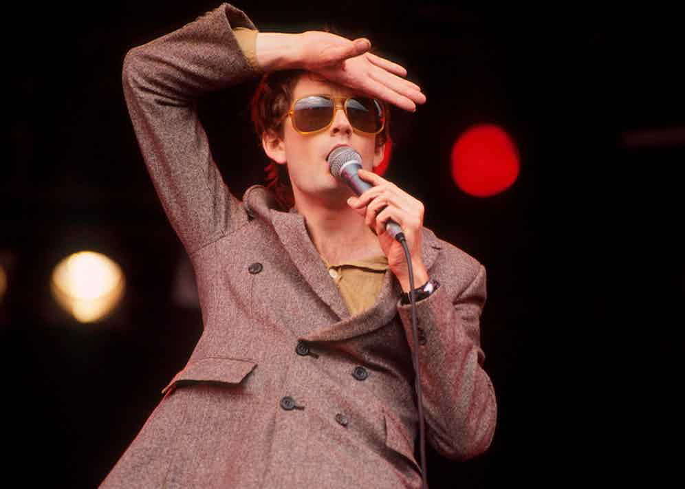 Jarvis Cocker of Pulp performs on stage at Glastonbury Festival, June 1994. Photo by Michael Putland/Getty Images.