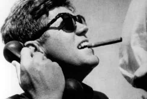 John F. Kennedy with cigar and sunglasses. Photo by Alamy.