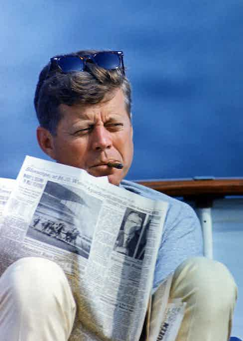 President John Kennedy smoking a cigar while reading the New York Times, aboard the family yacht, Honey Fitz in Hyannisport. Photo by Alamy.
