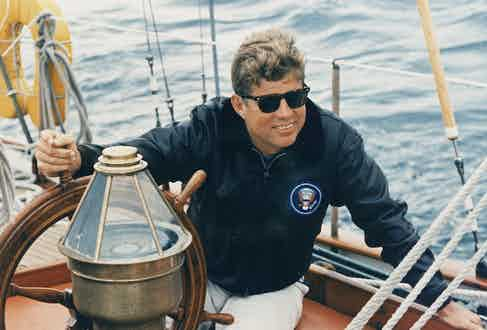 John F. Kennedy at the wheel of a US Coastguard yacht while on holiday in Maine on 12 August 1962. Photo by Alamy.