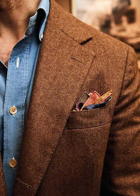A proud four-inch lapel on his bespoke Richard James sports coat in Joshua Ellis cashmere. He accessorises it with a Simonnot Godard pocket-handkerchief and denim shirt by Luca Avitabile as part of a collaboration between Avitabile and Permanent Style.