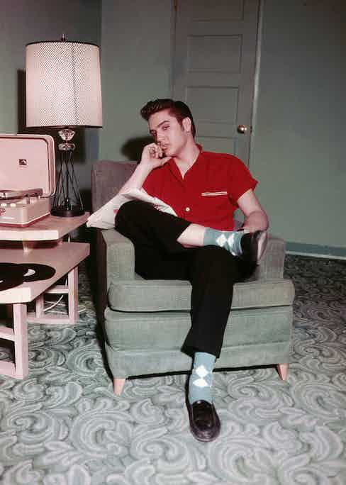 Elvis displaying his trademark insouciance with an argyle sock and penny loafer combination in 1956.